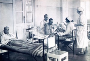 Рис. 8 А.И. Емельянов, заведующий терапевтическим отделением, на обходе осматривает больного.